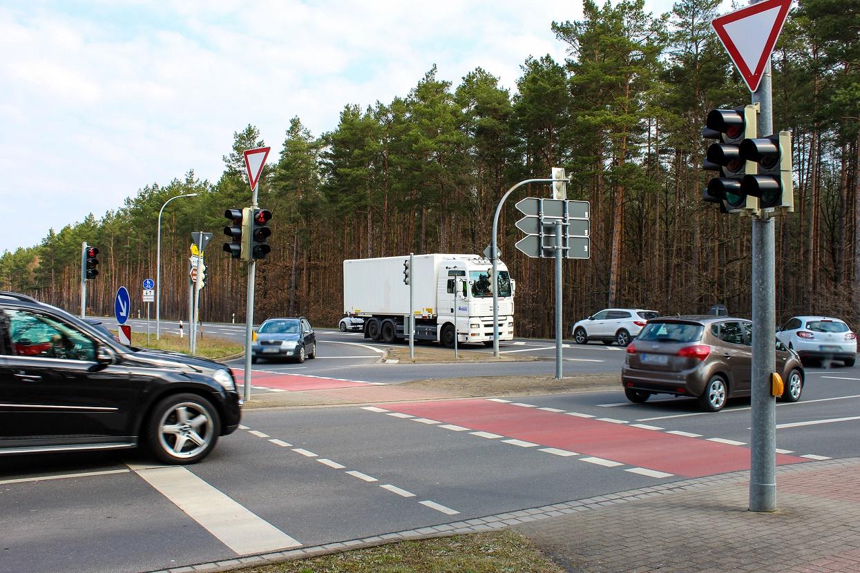Autos und ein LKW befahren eine Kreuzung.